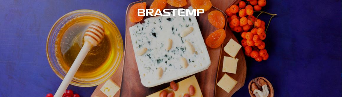 imagem de queijos e frutas em uma mesa azul.