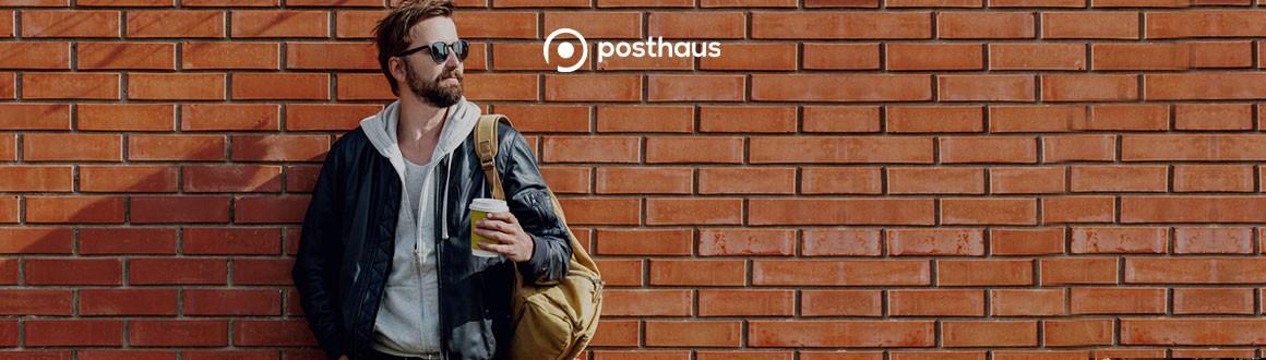 na imagem, homem encostado na parede de tijolos à vista, usando calça jeans, moletom cinza e jaqueta xadrez com óculos de sol e mochila.