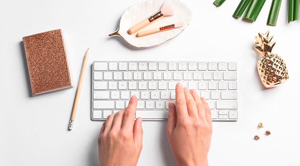 mulher com mãos em cima de um teclado e pincéis de maquiagem em cima da mesa
